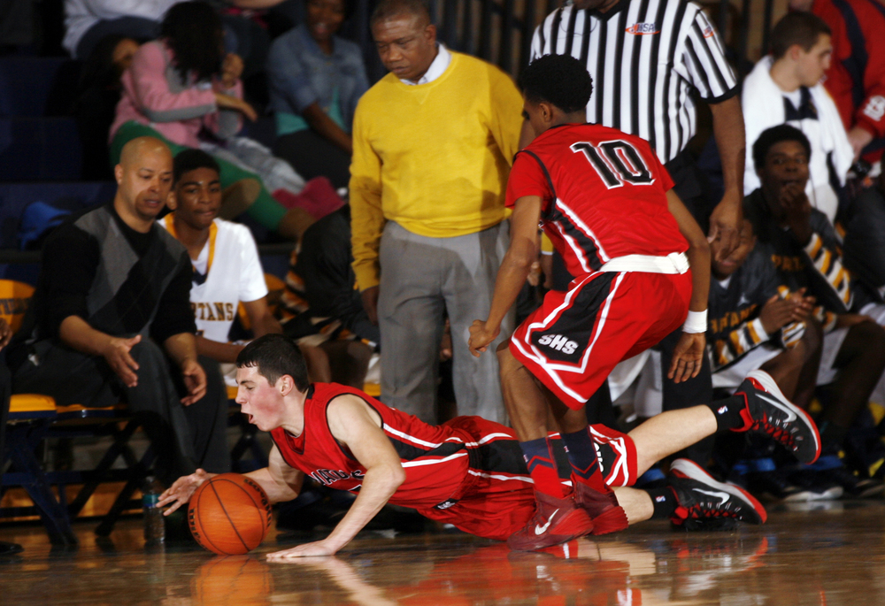 Springfield's Matt Sandberg dives for the ball in front of the Southeast bench at Southeast High School Tuesday Dec. 9, 2014. Ted Schurter/The State Journal-Register