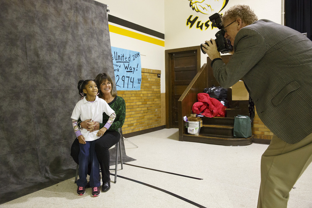 Ed Clark takes a picture of Harvard Park second-grader Kountess Masters-Stout with her lunch buddy, Michelle Buscher Wednesday Dec. 10, 2014. Buscher and 41 other Department of Corrections employees spent their lunch hour with a Harvard Park student before sharing gifts with them. It's the ninth year they've been to the school. Rich Saal/The State Journal-Register