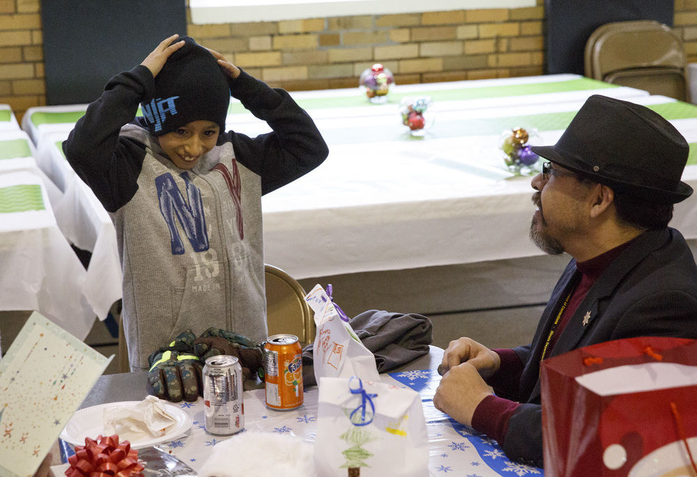 Fourth-grader Antonio Hernandez received new clothes, including a hat and a sweatshirt, from Felipe Zavala during their lunch Wednesday, Dec. 10, 2014. Rich Saal/The State Journal-Register