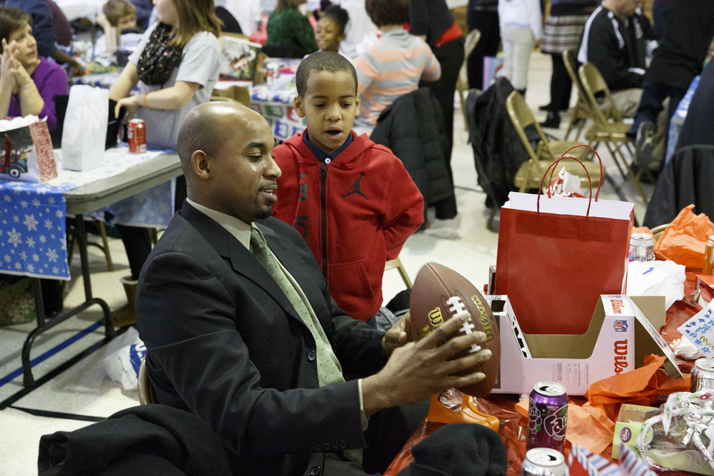 Glen Austin shows Corey Ballard how to grip his new football Wednesday, Dec. 10, 2014 at Harvard Park school. Rich Saal/The State Journal-Register