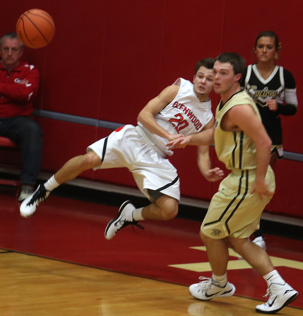 Titans player Ethan Hunt goes airborne out-of-bounds while deflecting the ball back into play as Cyclones player Gabe Green watches. Chatham Glenwood defeated Sacred Heart Griffin 54-40 in boys basketball action at Glenwood High School on Friday evening, Dec. 12, 2014. David Spencer/The State Journal-Register
