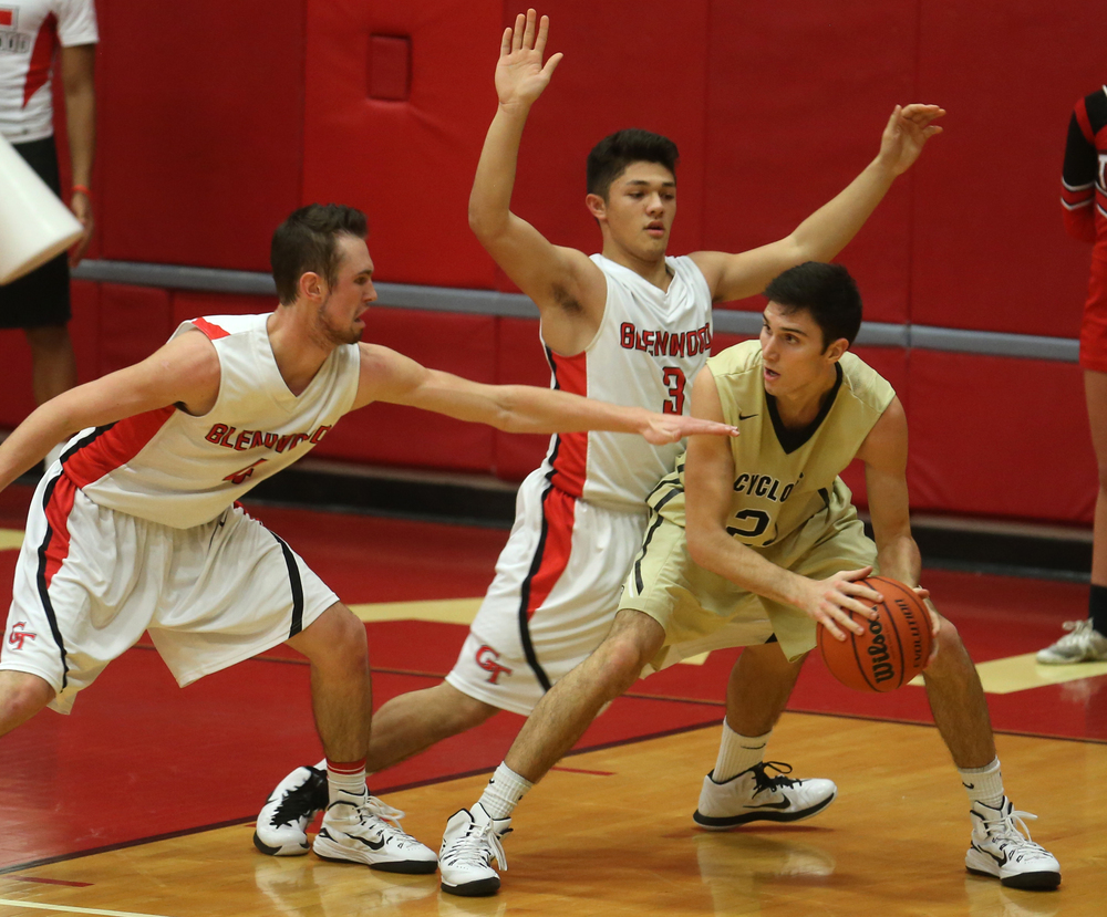 Cyclones player Ben Sestak looks for an open man while being defended by Glenwood players Sam Anderson at left and Drew Parriott. Chatham Glenwood defeated Sacred Heart Griffin 54-40 in boys basketball action at Glenwood High School on Friday evening, Dec. 12, 2014. David Spencer/The State Journal-Register