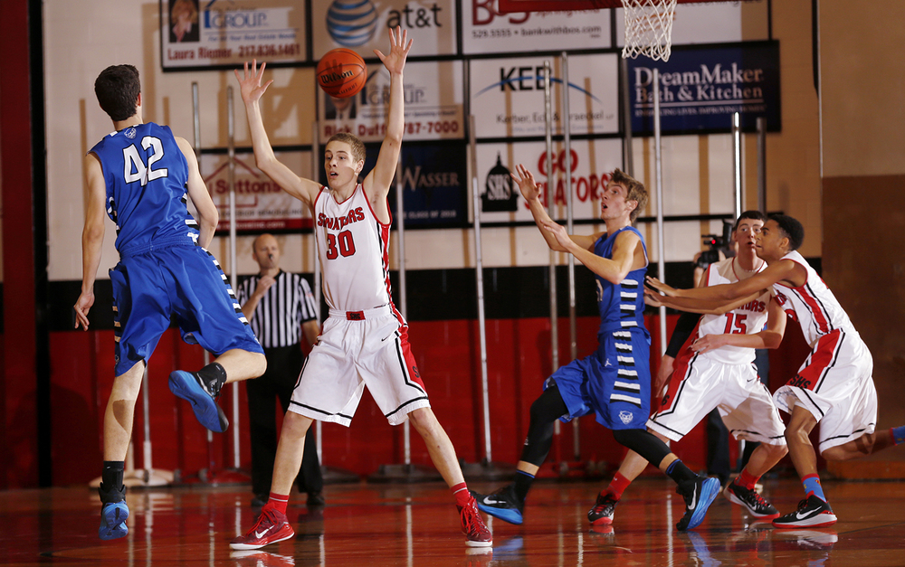 Quincy's Clayton Weirather fires a pass through the arms of Springfield's Blain Keene at Springfield High School Saturday, Dec. 13, 2014. Springfield High fell 50-49.  Read the game story.  Ted Schurter/The State Journal-Register
