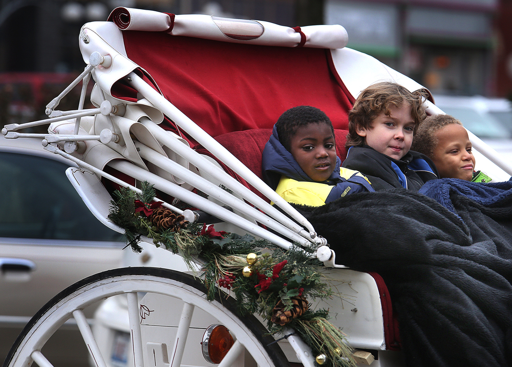 "Keeping warm under heavy blankets while seated for a ride in the open-air carriage Saturday are left to right: Nathan, 5, Sean, 10, and Aiden Londrigan, 6. Sean and Danielle Londrigan of Petersburgh's Red Gate Farm gave horse-drawn carriage rides around the Petersburg town square during the ""Christmas in Petersburg"" event on Saturday, Dec. 6, 2014.  David Spencer/The State Journal-Register"