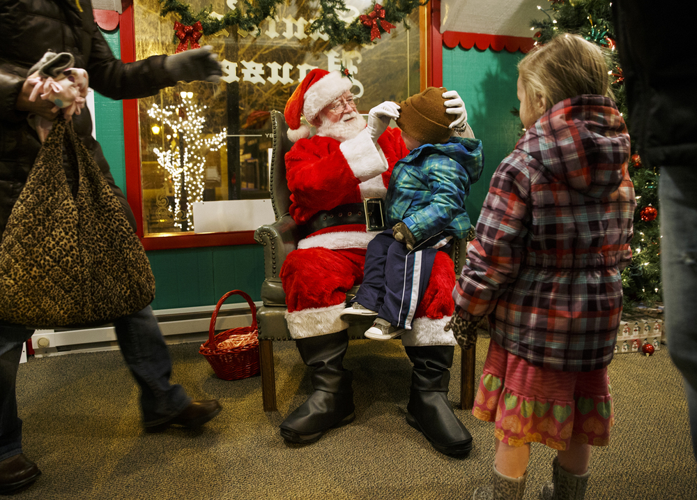 Santa Claus, portrayed by Jim Cox, prepares two-year-old Jax Washam for his photo with his sister Hadley as their mother Cara moves in to remove his hat at the Santa House at the Old State Capitol Plaza Wednesday, Dec. 10, 2014. Ted Schurter/The State Journal-Register