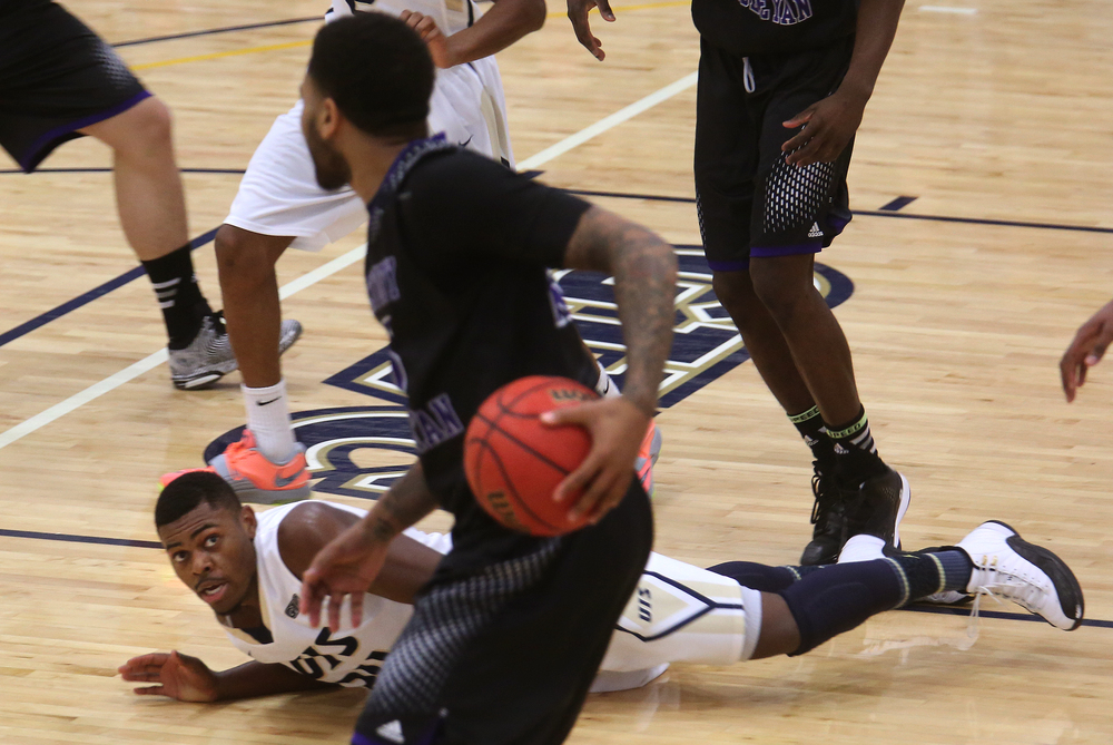 Stars player Jamall Millison keeps his eye on the ball despite landing on the floor. The Kentucky Wesleyan Panthers defeated the UIS Prairie Stars 80-61 in men's basketball action at the TRAC center on the UIS campus on Sunday, Dec. 14, 2014. David Spencer/The State Journal-Register