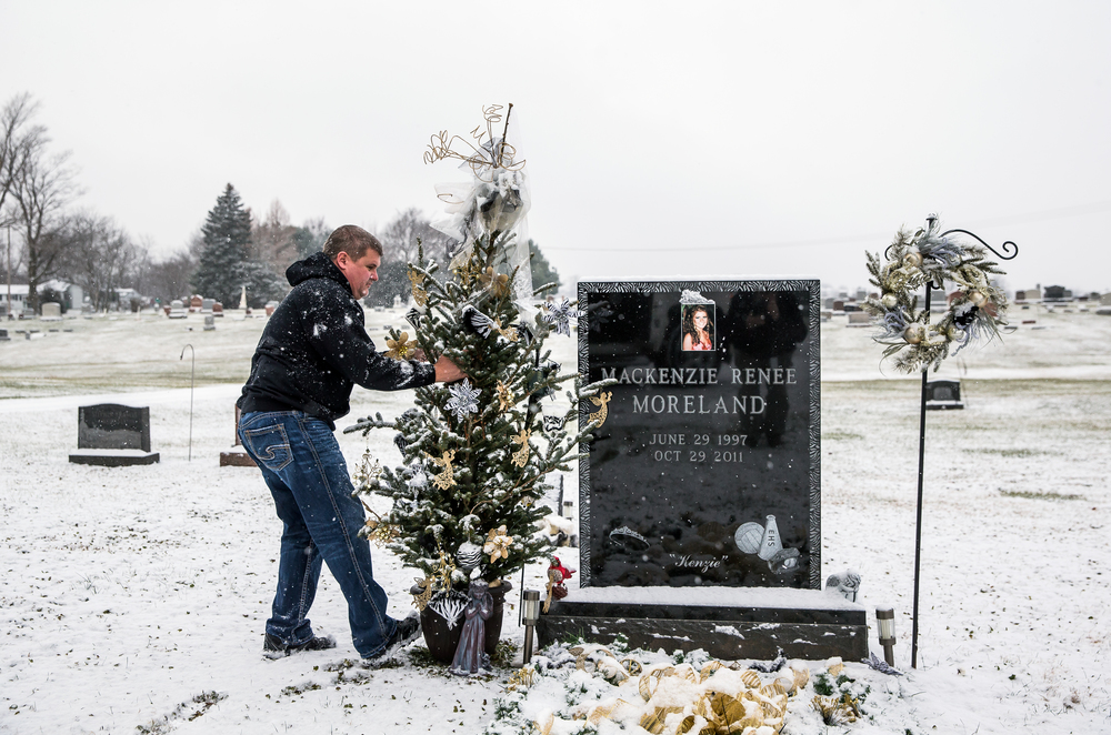 Ron Moreland stopped by the gravesite of his daughter, Mackenzie Morelane, to straighten the Christmas tree while on his route delivering gifts and clothes in her memory during the gift distribution for Kenzie's Christmas Wish, Thursday, Dec. 18, 2014, in Edinburg, Ill. Justin L. Fowler/The State Journal-Register