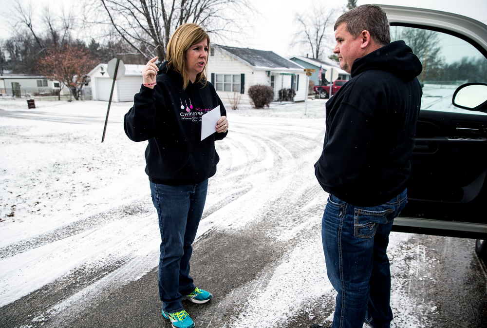 Erika Moreland, left, meets with her husband Ron Moreland, right, to drop off a package of gifts to be delivered along his route during the gift distribution for Kenzie's Christmas Wish, Thursday, Dec. 18, 2014, in Edinburg, Ill. Over 1600 toys and clothes were being to delivered to over 70 families in the area in honor of their daughter, Mackenzie Moreland. Justin L. Fowler/The State Journal-Register