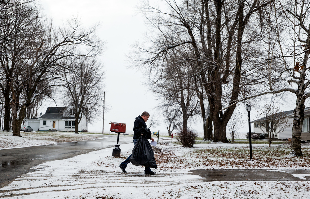 Ron Moreland makes his way down a driveway with a package of clothes and toys for a family in need during the gift distribution for Kenzie's Christmas Wish, Thursday, Dec. 18, 2014, in Edinburg, Ill. Justin L. Fowler/The State Journal-Register