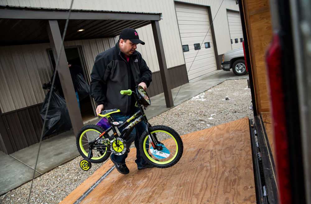 Joe Morell, a life long friend of Ron Moreland, loads a bicycle into the trailer for delivery along with packages of clothes and gifts during the gift distribution for Kenzie's Christmas Wish, Thursday, Dec. 18, 2014, in Edinburg, Ill. Morell has been a volunteer helping with Kenzie's Christmas Wish since it started in 2012. Justin L. Fowler/The State Journal-Register