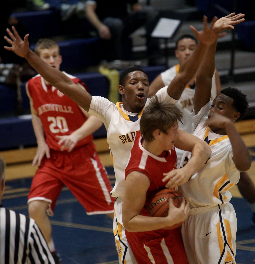 Spartan players Sabree Bakari at middle back and Mark Johnson at right defend while Crimsons player Joe Brannon tries to fight his way out of the situation. The Springfield Southeast High School Spartans defeated the Jacksonville High School Crimsons 60-36 in boys basketball action at the Spartans gym on Friday, Dec. 19, 2014. David Spencer/The State Journal-Register