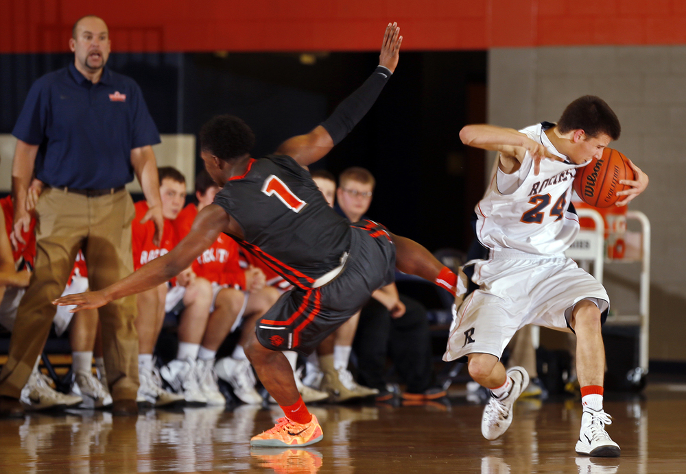 Lanphier's Yaakeema Rose and Rochester's Howard Fisher collide at midcourt at Rochester High School Saturday, Dec. 20, 2014. Ted Schurter/The State Journal-Register