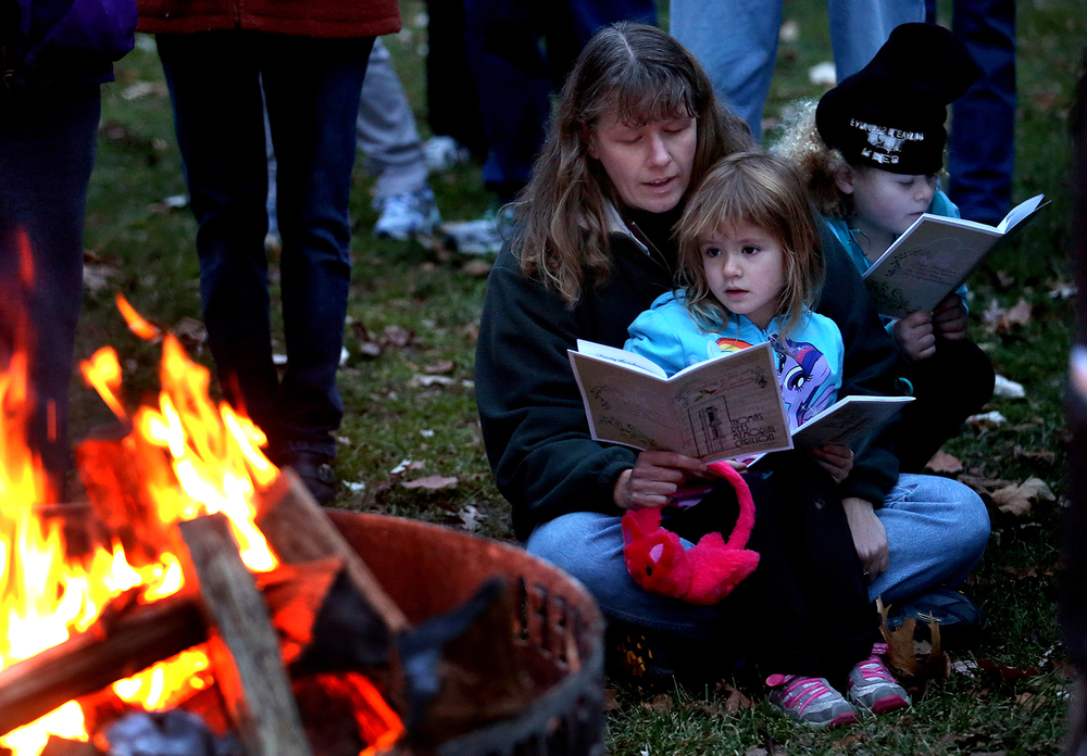 Elise Holt and her daughters, Ada, 4, on her lap, and Tia, 7, sing along at Caroling at the Carillon, an annual community sing-along hosted by the Carillon Belles & Springfield Park District at the Rees Memorial Carillon in Washington Park Sunday, Dec. 14, 2014. David Spencer/The State Journal-Register