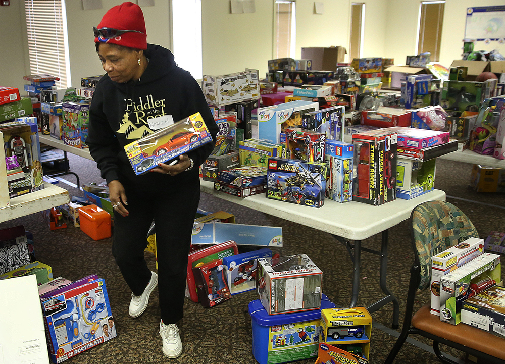 Salvation Army Adult Rehabilitation Center volunteer Noreen Fisher helps to pick out toys for a family during the Salvation Army's toy and food distribution Thursday, Dec. 18, 2014. David Spencer/The State Journal-Register