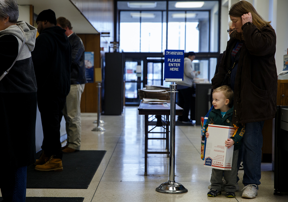 Eddie Longcore, 2, helps carry a package for his mother, Sabrina Longcore,  as they wait in line at the Cook Street Post Office, Monday, Dec. 15, 2014, in Springfield, Ill. Monday was anticipates as one of the Post Offices' busiest days of the year for mailing items for the holiday season. Justin L. Fowler/The State Journal-Register