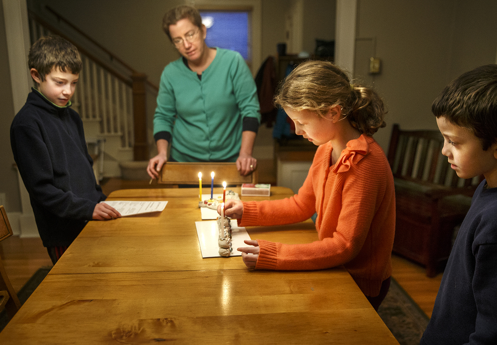 Hannah Knuuti returns the shamash, the attendant candle of a menorah used to light the other candles, to its place after lighting the first candle of her menorah in observance of the first night of Hanukkah Tuesday, Dec. 16, 2014. Joining Hannah at the table were her brothers Sam, left, and Nate and her mother Kim. One candle is lit for each of the eight nights of the Jewish holiday, also known as the Festival of Lights. Ted Schurter/The State Journal-Register