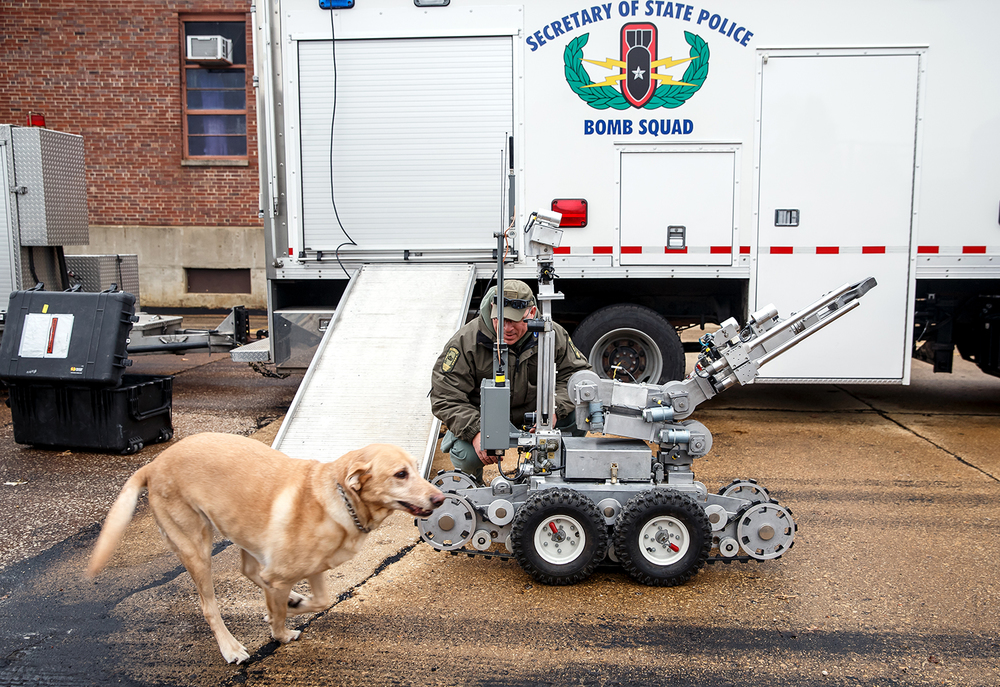 Investigator Ron Lewis, of the Illinois Secretary of State Police, works with the bomb squad's remote controlled robot along with one of the unit's dog, Beck, prior to a scenario during training exercises for the Illinois Statewide Weapons of Mass Destruction Team on the grounds of the former Jacksonville Developmental Center, Tuesday, Dec. 16, 2014, in Jacksonville, Ill. The robot is equipped with multiple cameras and tools that allow the operators to deal with hazardous devices from a safe distance. Justin L. Fowler/The State Journal-Register