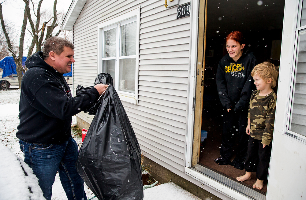 Katherine Marta and her son Preston Marta, 4, greet Ron Moreland with a smile as he delivers a package of gifts and clothes in the snow to the family during the gift distribution for Kenzie's Christmas Wish , Thursday, Dec. 18, 2014, in Edinburg, Ill. Kenzie's Christmas Wish provides gifts and clothes in memory of Mackenzie Moreland, the daughter of Ron and Erika Moreland who passed away in 2011 from a heart condition called myocarditis. Justin L. Fowler/The State Journal-Register