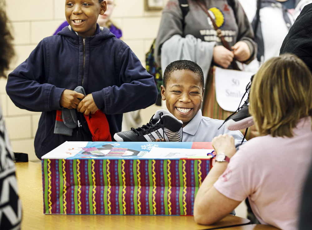Jy're Ray smiles as he shows Washington Middle School teacher Ann Kuehnel a pair of shoes he received during the Fifty Smiles event Friday, Dec. 19, 2014. Darryl Williams organized the annual event and secured donations to provide more than 100 students with gift bags. Ted Schurter/The State Journal-Register