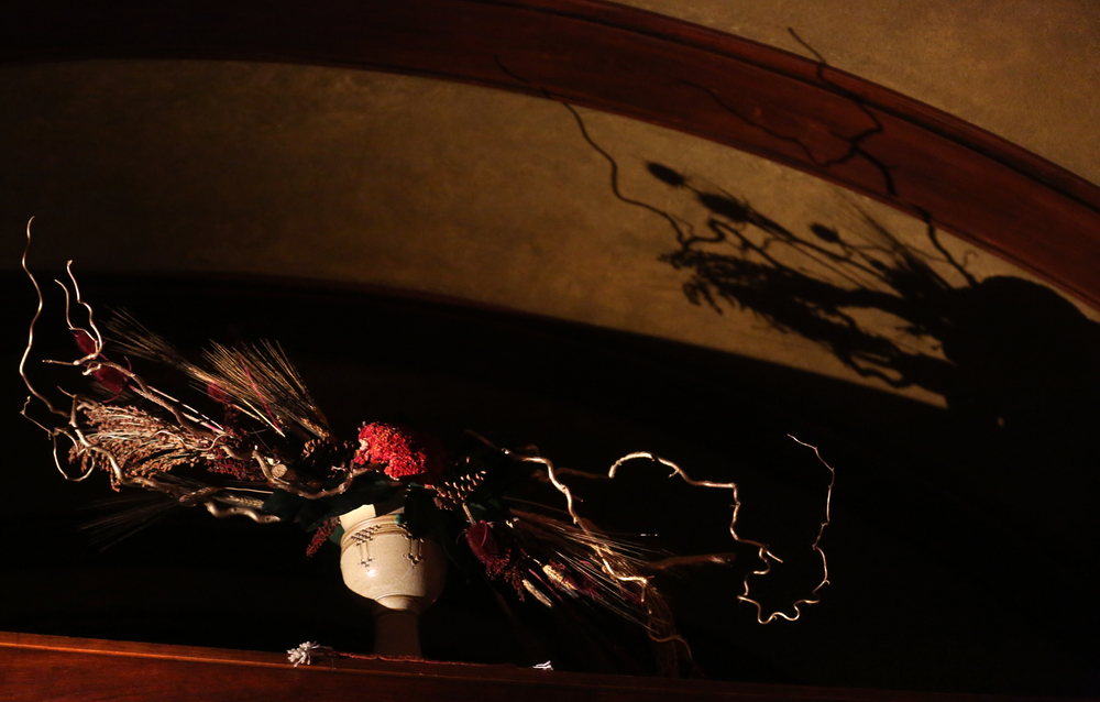 The Springfield Civic Garden Club supplied holiday floral arrangements for the home, including this one casting shadows onto the ceiling high above the gallery.