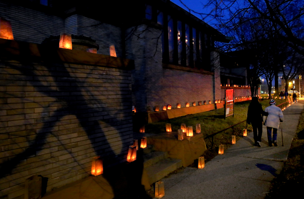 Visitors make their way to the home's front entrance to begin a tour while shadows from a tree are cast onto the home's exterior lit by some of the luminarias.
