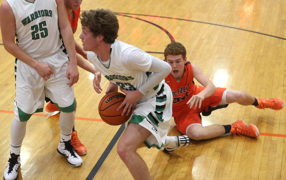 Warriors player Ryan Freer goes to the basket after colliding with Pretzels defender Hunter Stockton on floor at right. Athens defeated New Berlin 83-54 on first day action at the Waverly Holiday basketball tournament in Waverly on Friday, Dec. 26, 2014. David Spencer/The State Journal-Register