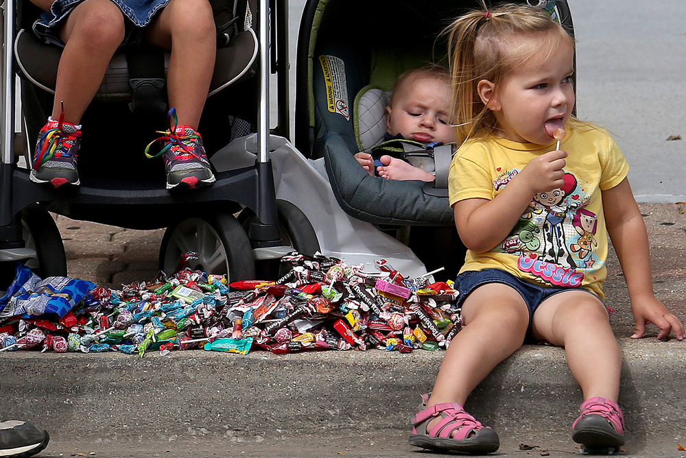 No bags? No problem. Candy piles up at the feet of children along Fifth Street near the end of the Springfield and Central Illinois Trades and Labor Council's annual Labor Day parade Sept. 1, 2014. David Spencer/The State Journal-Register