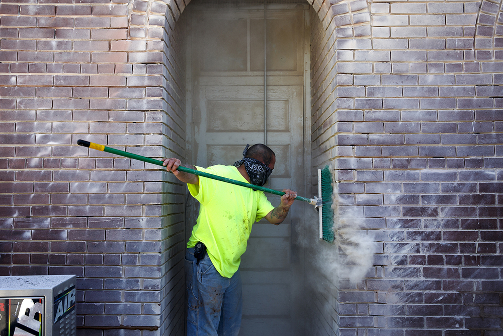 Tony Fry sweeps a brick doorway in the Loami County Market during a tuckpoint and seal project on the building Friday, Sept. 19, 2014. Fry Tuckpointing is repairing the 109-year-old building, which once served as the Loami Town Hall. Rich Saal/The State Journal-Register