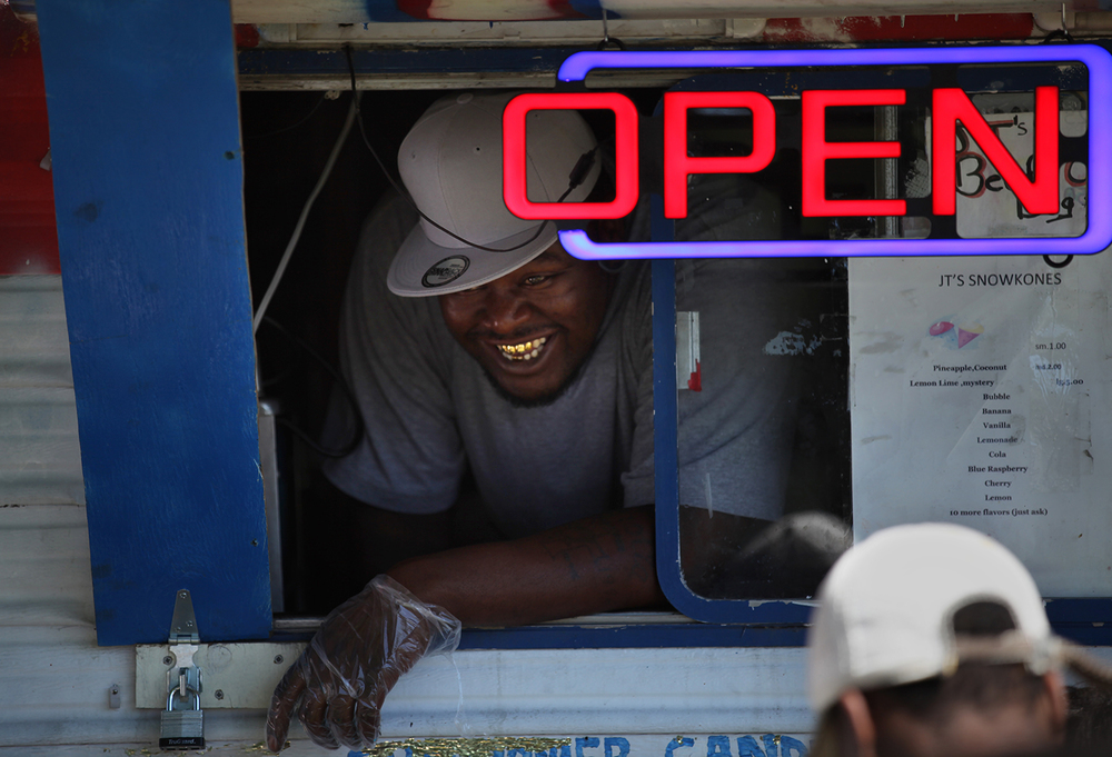 Matthew Jones offers a smile with service from JT's snack truck during the Juneteenth celebration at Comer Cox Park Saturday, June 14, 2014. Rich Saal/The State Journal-Register
