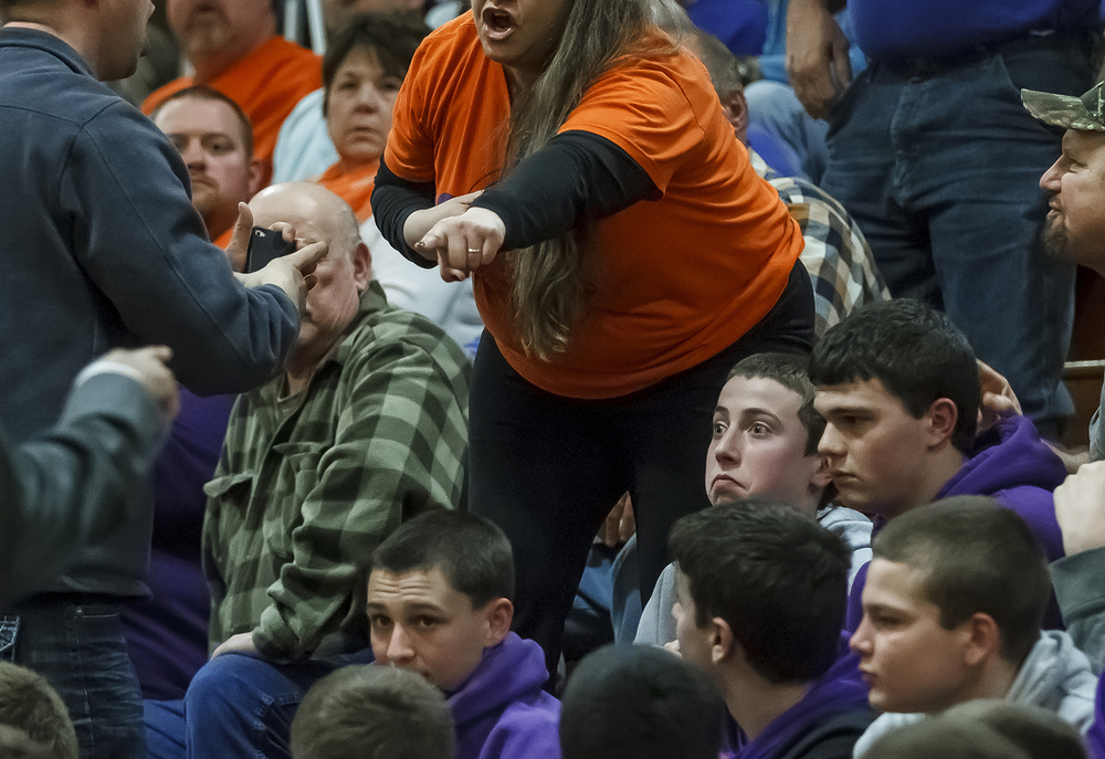 A young Williamsville fan is stuck in the middle as a Riverton fan is asked to leave the game by security during the Class 2A Williamsville Regional semifinals at Williamsville High School, Tuesday, Feb. 25, 2014, in Williamsville, Ill. Justin L. Fowler/The State Journal-Register
