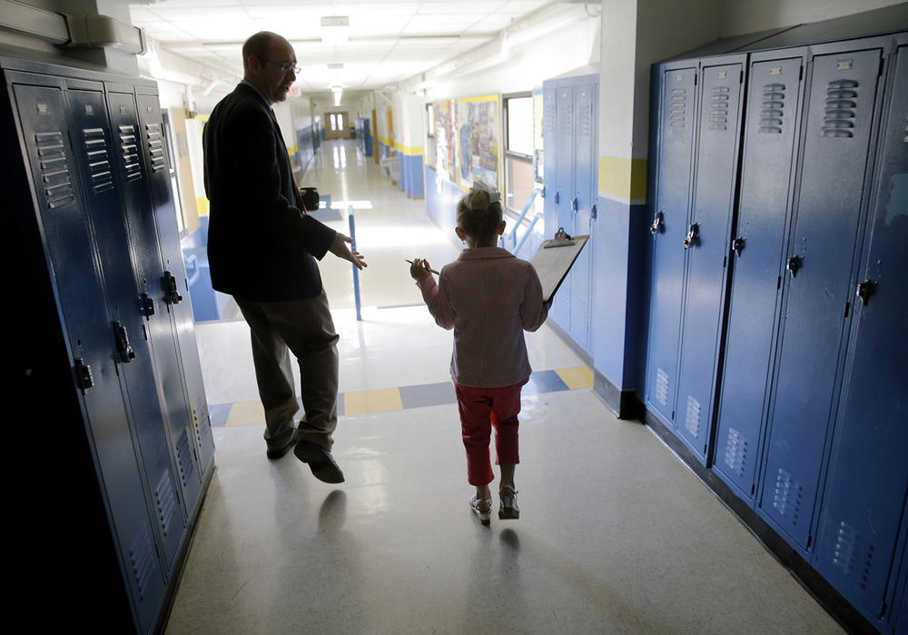 Five-year-old Taryn Clarke speaks with Tri-City Middle and High School principal Dustin Day as she tours the facilities during her time as principal for a day Wednesday, April 9, 2014. Ted Schurter/The State Journal-Register