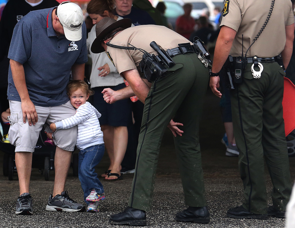 Adaline Jasinski, 2, of New Lenox, Ill., clings to her father David Jasinski while making the acquaintance of Illinois State Police trooper Joshua Heer at the Illinois State Fair in August. Adaline eventually exchanged a high-five with Heer. David Spencer/The State Journal-Register