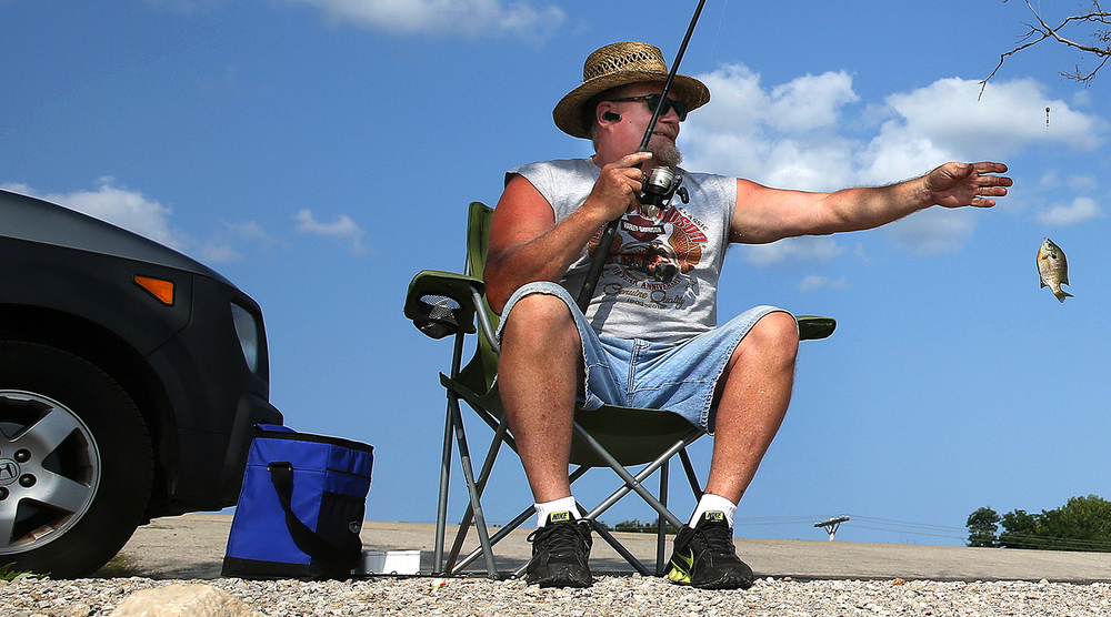 Todd Grider hauls in a fish on the shore of Lake Springfield July 29, 2014. David Spencer/The State Journal-Register
