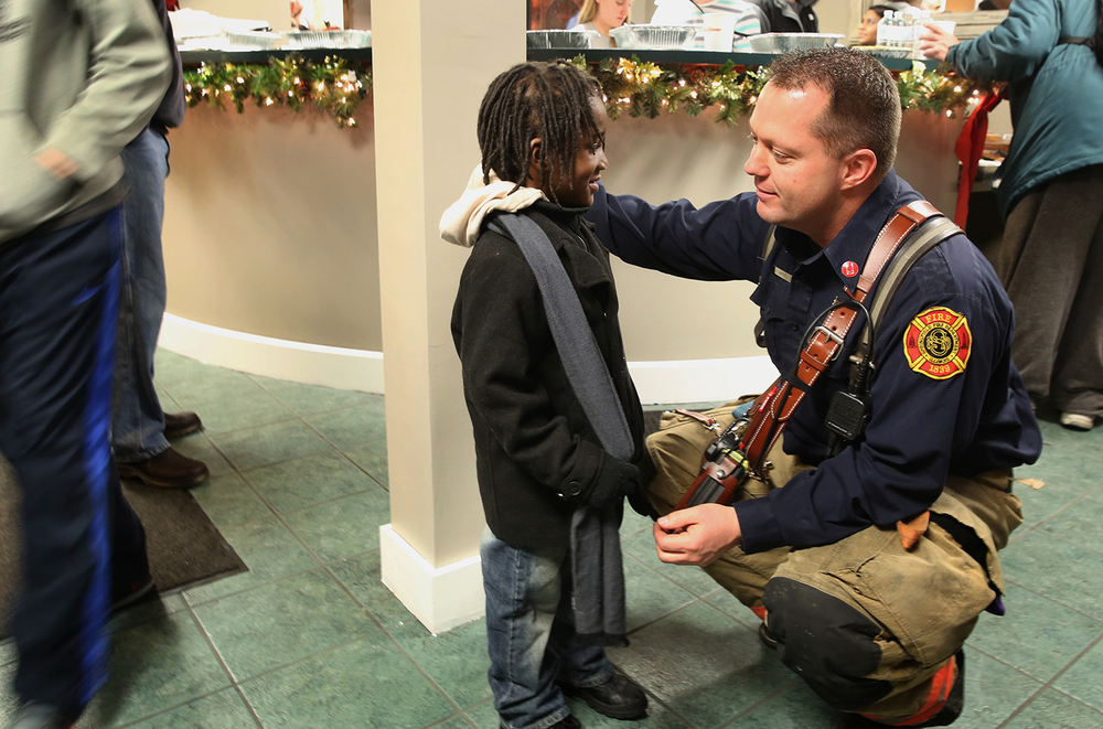 Springfield Firefighter Chad Bates talks to Jaden Peters, 3, who lives at The Stevenson Inn with his family. Bates and the crew from Station 2 supplied a holiday meal to about 50 residents of The Inn on Dec. 22, 2014. The meal was a result of a partnership between Springfield Fire Fighters Local 37, Springfield-based Midwest Medical and Bob Evans restaurant. Station 2 firefighters also purchased gifts for six children at the hotel. David Spencer/The State Journal-Register