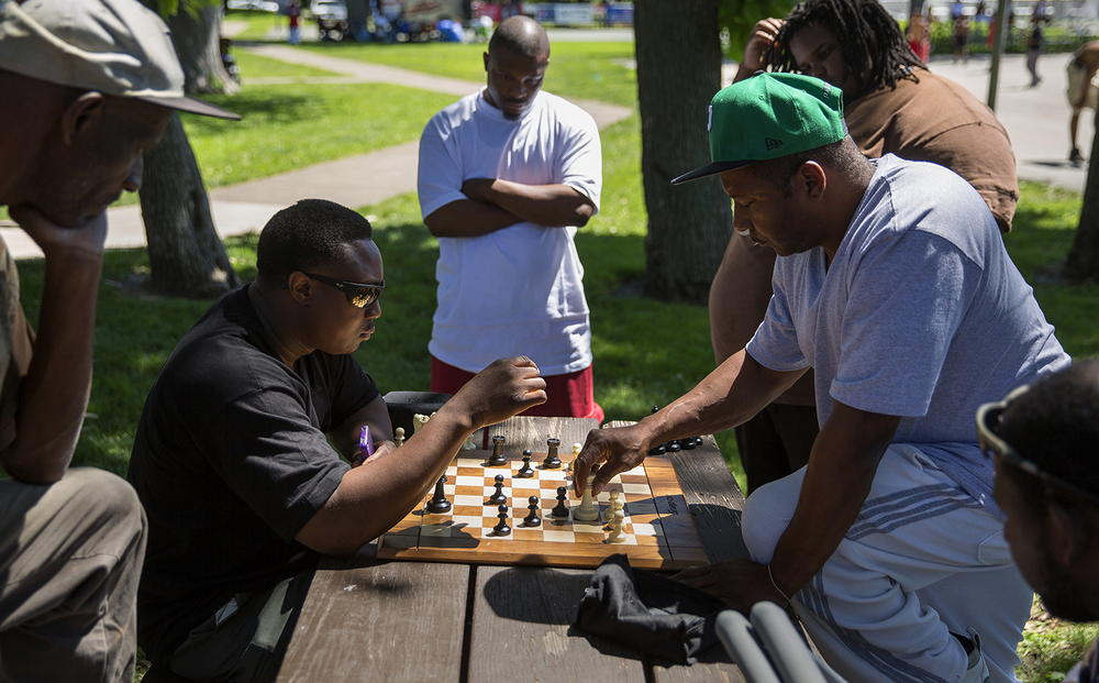 Portis Rice, left, and Eric Winkie Ellington face off across a chessboard during the Juneteenth celebration at Comer Cox Park Saturday, June 14, 2014. Rich Saal/The State Journal-Register