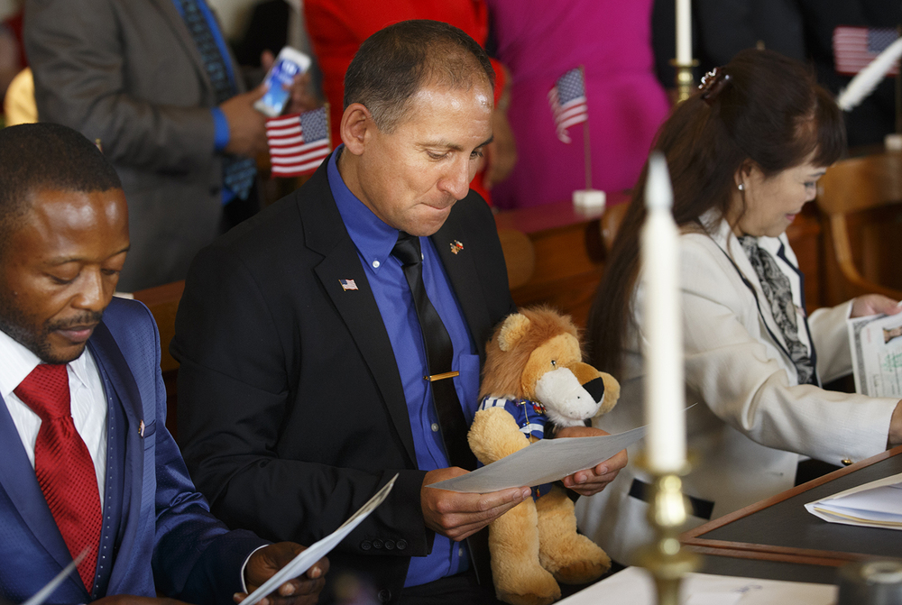 Manual Eduardo Alvarez Toro gazes at his new certificate of naturalization as he holds a toy lion during a ceremony at the Old State Capitol Friday, May 2, 2014. Toro said he carried the lion, given to him by his sister, because it reminded him of his family in Chile. Ted Schurter/The State Journal-Register
