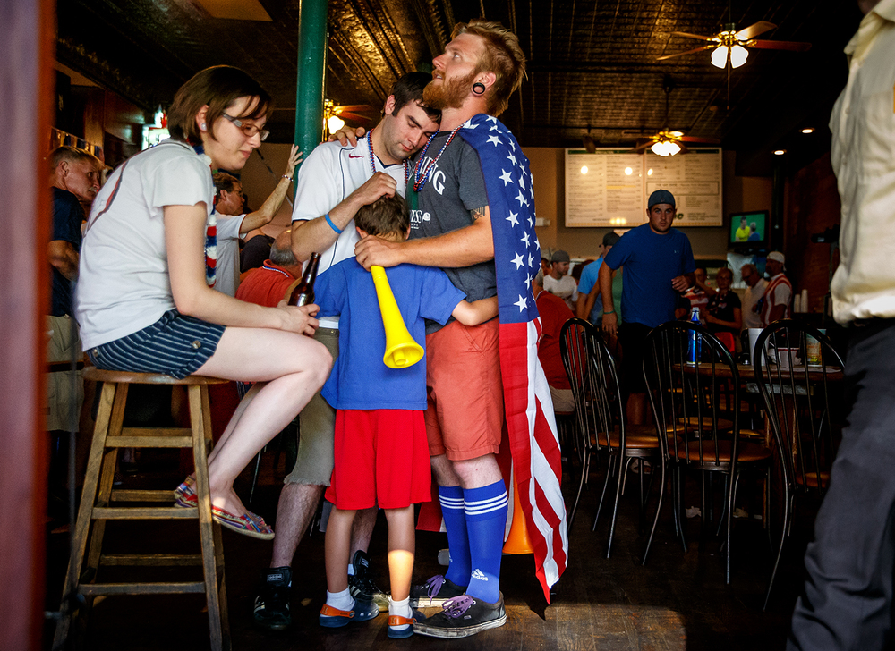 After USA was defeated by Belgium 2-1 in extra time Alex Owens, center, hugs Jake Sawyer and Jackson Stevens, 8, while watching the World Cup game during a viewing party hosted by The Land of Lincoln chapter of the American Outlaws at The Alamo, Tuesday, July 1, 2014, in Springfield, Ill. Justin L. Fowler/The State Journal-Register