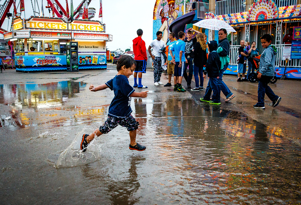 Aric Crosby, 3, leaps through a puddle of water in the carnival midway at the Illinois State Fairgrounds, Thursday, Aug. 7, 2014. A constant rain that fell throughout the preview night left plenty of puddles to choose from. Justin L. Fowler/The State Journal-Register