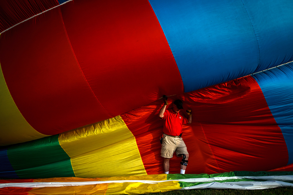 Chris Keefe, of Oshkosh, Wisc., holds back an inflating balloon at the Lincoln Art & Balloon Festival at the airport, Saturday, Aug. 23, 2014, in Lincoln. Justin L. Fowler/The State Journal-Register
