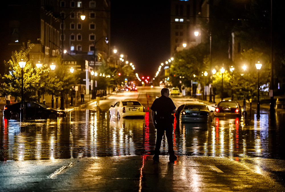 A Springfield police officer watches over the intersection of Sixth and Edwards streets where cars became stranded after two inches of rain fell in 30 minutes Aug. 28. Justin L. Fowler/The State Journal-Register
