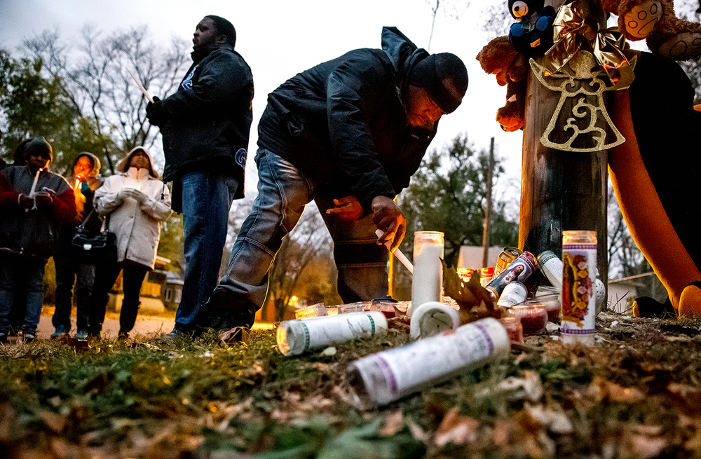 "Curtis Bounds, an outreach worker with the Springfield Urban League, lights a candle at the memorial for murder victim Kirk Handy after a peace walk to the site on Cass Street between 13th and 14th, Tuesday, Nov. 11, 2014. ""We're just trying to change the norms, change the realities...it's old, it's tiresome. We're just trying to make a difference, make a change."" said Bounds on the peace walk. ""We lost a father, a community member...gun violence it don't destroy one life, it destroys many."" Justin L. Fowler/The State Journal-Register"