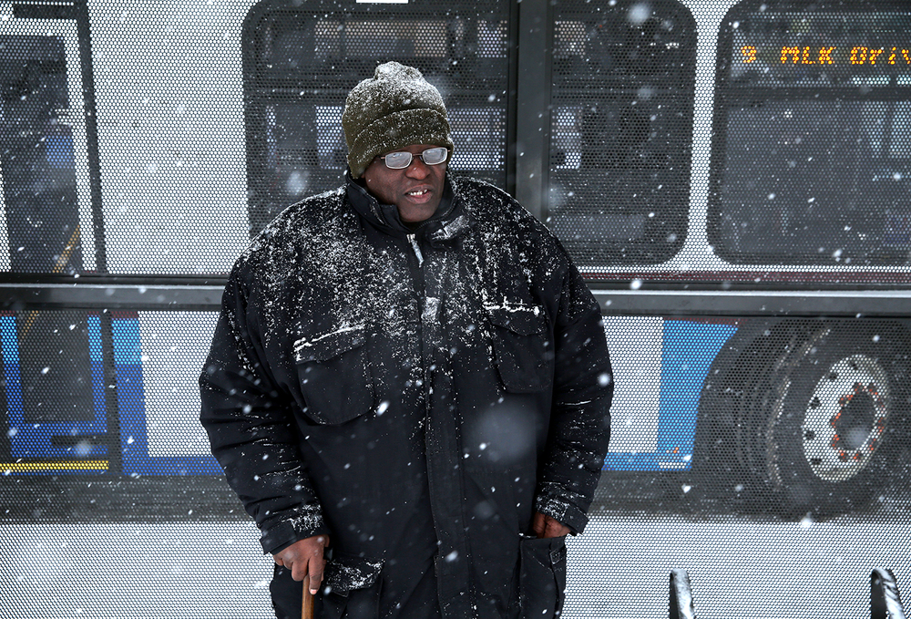 Anthony Drew is sheltered from most of the snow while waiting for a bus on Capitol Avenue near Fifth Street Tuesday, Feb. 4, 2014. Rich Saal/The State Journal-Register