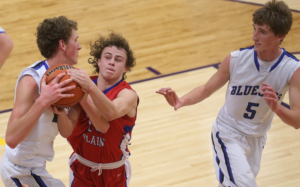 Bluejays player Max Muller, left, fights for the ball with Cardinals player Cole Greer. At right is Bluejays player Matt Muller. Petersburg PORTA defeated Pleasant Plains 58-50 on the second day of action at the Williamsville Holiday basketball tournament at Williamsville High School on Saturday, Dec. 27, 2014. David Spencer/The State Journal-Register