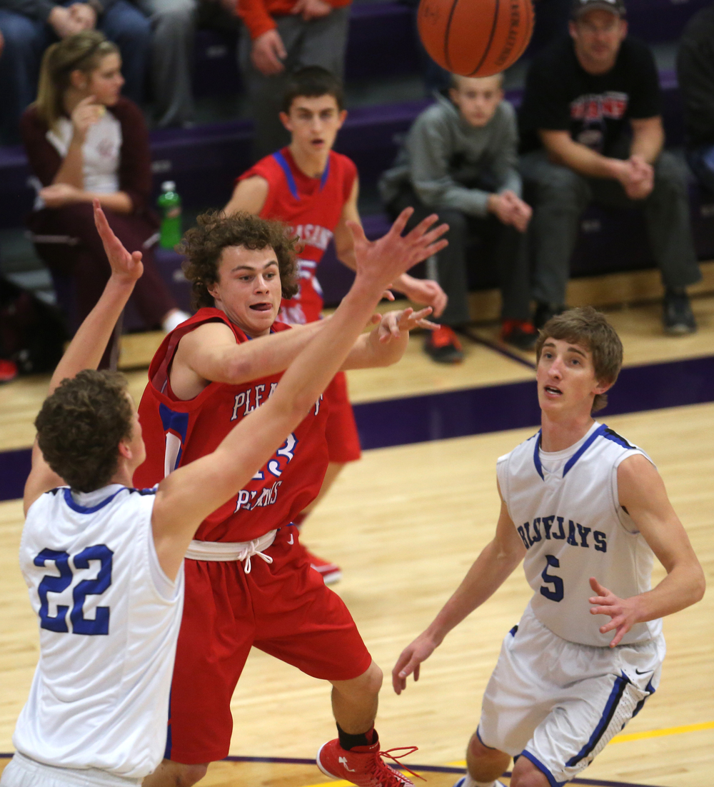 Cardinals player Cole Greer dishes off the ball under pressure from Bluejay players Max Muller at left and Matt Muller. Petersburg PORTA defeated Pleasant Plains 58-50 on the second day of action at the Williamsville Holiday basketball tournament at Williamsville High School on Saturday, Dec. 27, 2014. David Spencer/The State Journal-Register