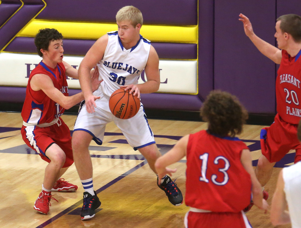 Bluejays player Michael McCurdy looks to get around Cardinals defender Daulton Nibbe. Petersburg PORTA defeated Pleasant Plains 58-50 on the second day of action at the Williamsville Holiday basketball tournament at Williamsville High School on Saturday, Dec. 27, 2014. David Spencer/The State Journal-Register