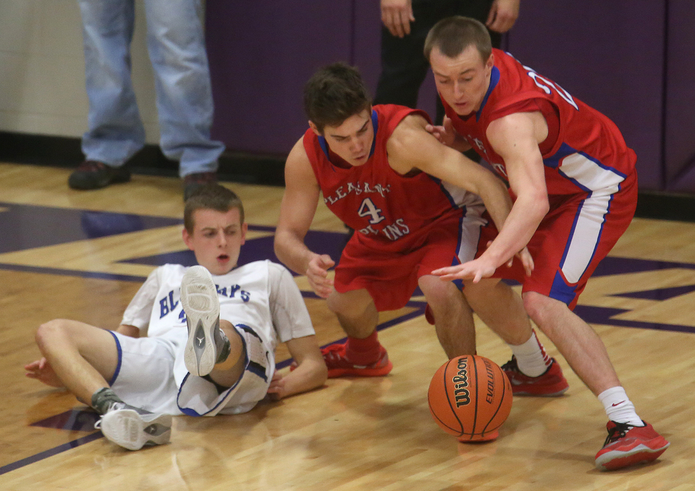 Cardinal teammates Aden Sachs at middle and Dylan Bee each go for the ball while Bluejays defender Michael Curry looks on from the floor during first half action. Petersburg PORTA defeated Pleasant Plains 58-50 on the second day of action at the Williamsville Holiday basketball tournament at Williamsville High School on Saturday, Dec. 27, 2014. David Spencer/The State Journal-Register
