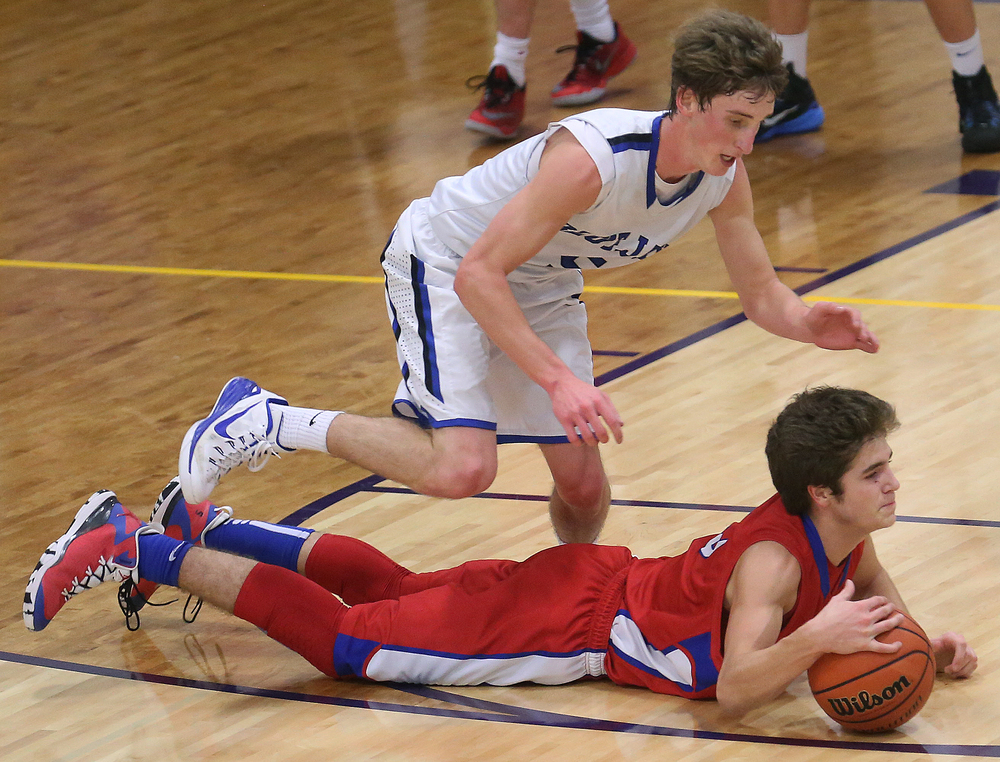 In second half action, Cardinals player Landon Davis keeps possession of the ball while prone on the floor while Bluejays player Matt Muller looks for an opening to strip the ball from him. Petersburg PORTA defeated Pleasant Plains 58-50 on the second day of action at the Williamsville Holiday basketball tournament at Williamsville High School on Saturday, Dec. 27, 2014. David Spencer/The State Journal-Register