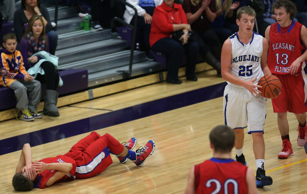 Cardinals player Landon Davis composes himself while on the floor after fighting for the ball with Bluejays player Seth Rebbe at right. Davis was not hurt. Petersburg PORTA defeated Pleasant Plains 58-50 on the second day of action at the Williamsville Holiday basketball tournament at Williamsville High School on Saturday, Dec. 27, 2014. David Spencer/The State Journal-Register
