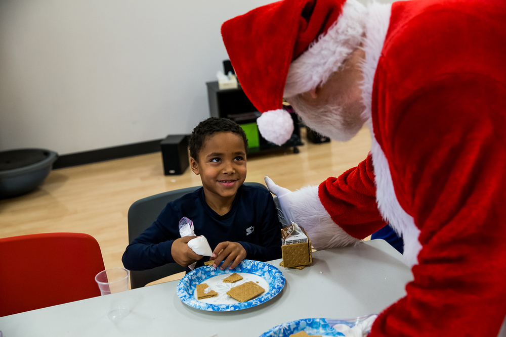Isaiah Gadbois, 6, gets a visit from Santa Claus as he starts to glue pieces of his house together with icing during the Gingerbread House Make and Take program at the Kerasotes YMCA, Monday, Dec. 22, 2014, in Springfield, Ill. Justin L. Fowler/The State Journal-Register
