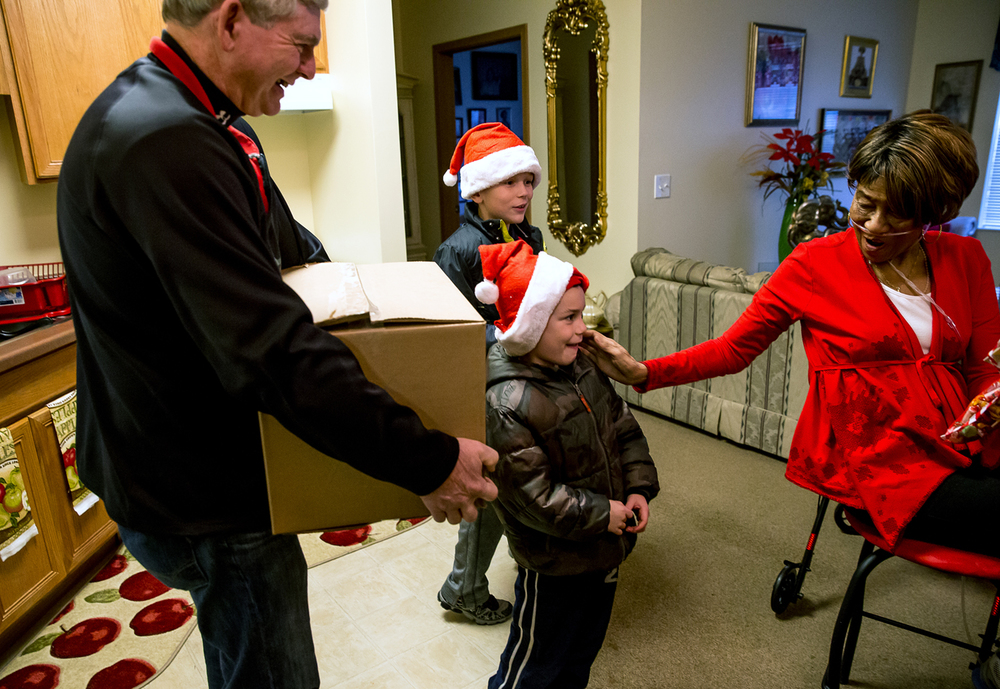 Anna Richie, right, thanks Cruz Evans, 6, center, of Chatham, Ill., and his brother, Drew Evans, 8, as they delivered two boxes of food along with their grandfather Gary Evans, left, of Spaulding, Ill., to her apartment in Timberlake Estates during the Friend-in-Deed food delivery, Tuesday, Dec. 23, 2014, in Springfield, Ill. This was the first time for Evans participating in Friend-in-Deed and he hopes to make it an annual tradition for his family. Justin L. Fowler/The State Journal-Register